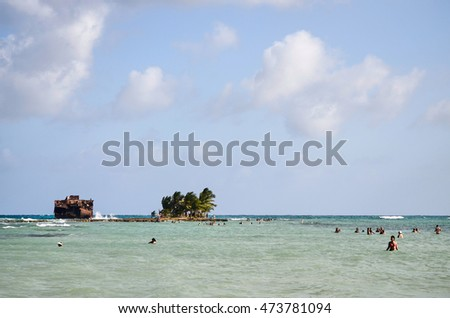 SAN ANDRES, COLOMBIA - JANUARY 10, 2015: The shipwreck of Rocky Cay in San Andres, with some tourists visiting it.