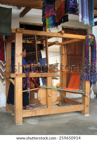 SAN ANTONIO DE PALOPO, GUATEMALA-MAY 15, 2007: A Guatemalan woman demonstrates the use of a foot-treadle floor loom. Weaving is a major money maker for women in the Lake Atitlan region of the country. - stock photo
