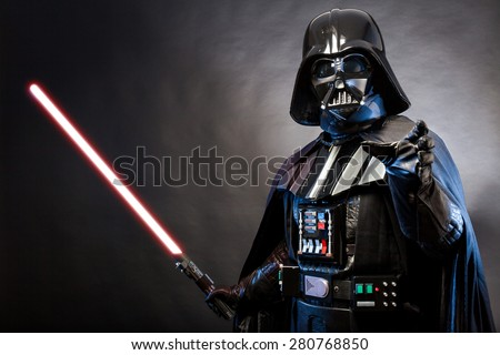 SAN BENEDETTO DEL TRONTO, ITALY. MAY 16, 2015. Portrait of Darth Vader costume replica with grab hand and his sword . Darth Vader is a fictional character of Star Wars saga.  Blue grazing light  - stock photo