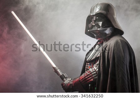SAN BENEDETTO DEL TRONTO, ITALY. MAY 16, 2015. Portrait of Darth Vader costume replica with his sword . Lord Fener is a fictional character of Star Wars saga.  Red backlight and smoke - stock photo