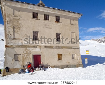 San Bernardino, Switzerland - January 8, 2015: Old hotel in step used as summer bar for passing tourists along the scenic route. Tourist sitting on the steps of entry. - stock photo