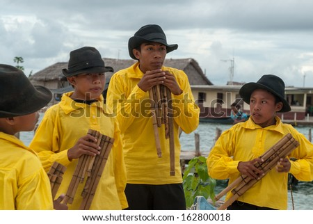 SAN BLAS ISLANDS - CIRCA JUNE 2006. Unknown native Kuna Indian children dressed  in native cerimonial attire playing hand made flutes in the San Blas Islands, panama, CIRCA June 2006.
