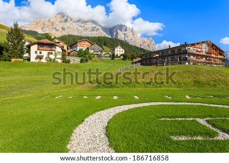 SAN CASSIANO, DOLOMITES, ITALY - SEPTEMBER 25, 2013: grass landing place for helicopter in alpine luxury hotel on September 25, 2013 in San Cassiano village, Italy.  - stock photo