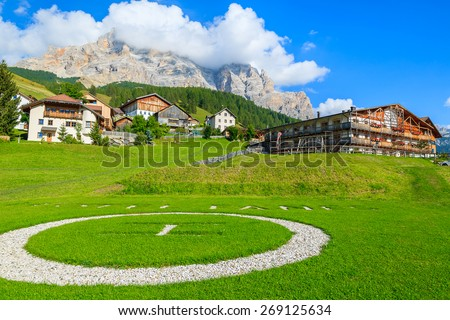 SAN CASSIANO, DOLOMITES MOUNTAINS, ITALY - SEP 25, 2013: helipad on green meadow with alpine hotel and houses in background. South Tyrol is northern part of Italt which is luxury tourist destination. - stock photo