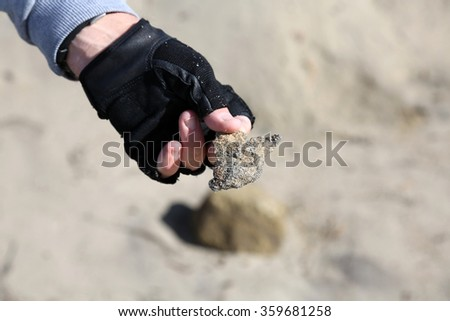San Clemente CA Jan. 7 2016: A man uses his Metal Detector as he sifts through the sand after the Godzilla El Nino of 2016. Here he shows a piece of scrap metal he found buried in the sand. - stock photo