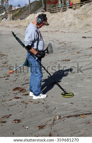 San Clemente CA Jan. 7 2016: A man uses his Metal Detector as he sifts through the sand after the Godzilla El Nino of 2016 hits the beach of San Clemente CA in hopes of finding lost buried treasure - stock photo