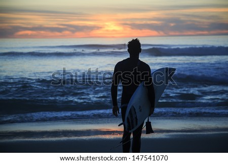 SAN DIEGO, CALIFORNIA - MARCH 02: Surfer enjoying sunset at Windansea Beach on March 02, 2013 in San Diego, California. Windansea Beach is one of the most famous places for surfing in San Diego,CA. - stock photo