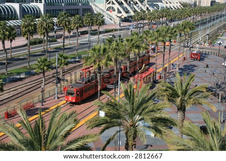 San Diego trolley along Harbour Drive at the Gaslamp stop.  Convention Center in the background. - stock photo