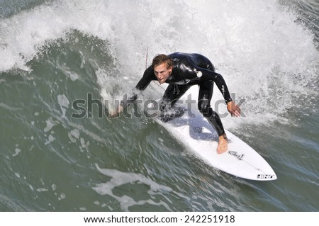 SAN DIEGO USA - SEPTEMBER 1st, 2014: Man in San Diego surfing. San Diego is very well known for surfing - stock photo
