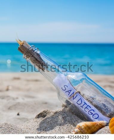 San Diego written in a bottle on an empty beach - stock photo