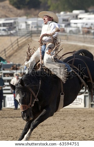 SAN DIMAS, CA - OCTOBER 2: Unidentified cowboy competes in the Saddle Bronc event at the San Dimas Rodeo on October 2, 2010 in San Dimas, CA. - stock photo