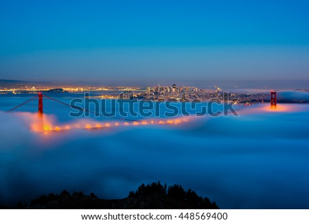San Francisco and Golden Gate Bridge on a foggy night  - stock photo