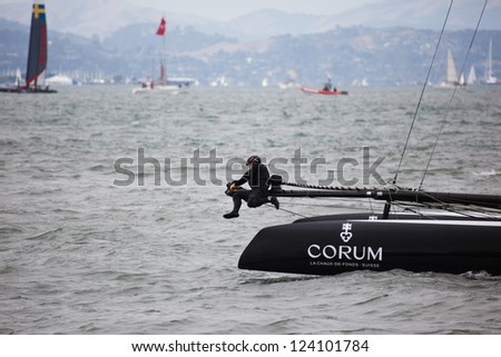 SAN FRANCISCO- AUGUST 25, 2012: A French Team Corum man hangs on tight in  Louis Vuitton Cup race in Americas Cup Series on August 25, 2012 in San Francisco, where cup finals will be held summer 2013. - stock photo