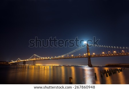 San Francisco Bay Bridge to Treasure Island at night.  Panoramic view with a full moon shinning behind the bridge. - stock photo