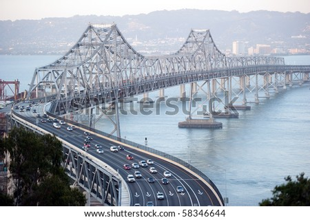 san francisco bay bridge with the city of oakland in the background - stock photo