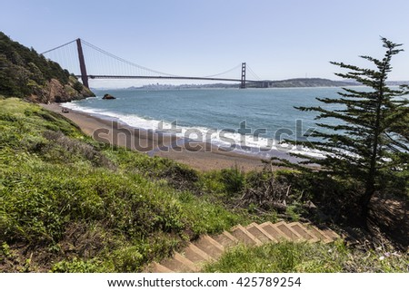 San Francisco Bay hiking trail and beach cove with view through Golden Gate Bridge in Golden Gate National Recreation Area. - stock photo