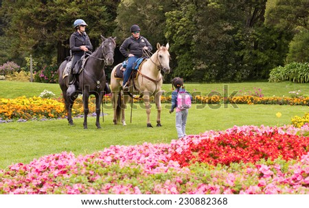 SAN FRANCISCO, CA - AUGUST 16, 2014 - San Francisco Police on Horse back with small girl in Golden Gate Park San Francisco. - stock photo