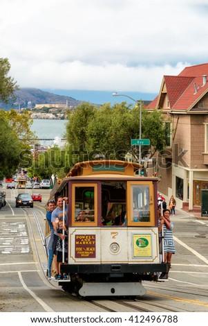 SAN FRANCISCO, CA - CIRCA JULY 2014 - People on Powell Hyde Cable cars traffic in San Francisco, CA, circa July 2014.  - stock photo