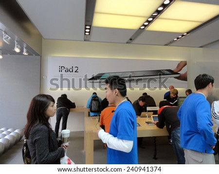 SAN FRANCISCO, CA - JUNE 27: People look at products and talk to sales reps inside Apple Store with Ipad 2 ad on wall in San Francisco California June 27 2011. - stock photo