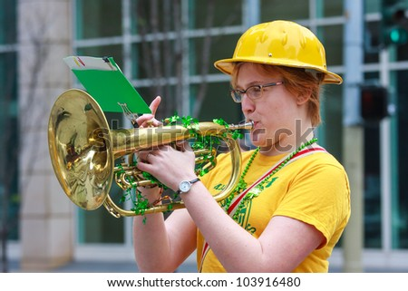SAN FRANCISCO, CA - MARCH 17: A woman playing saxhorn during the St. Patric's Day Parade. March 17, 2012 in San Francisco, CA - stock photo