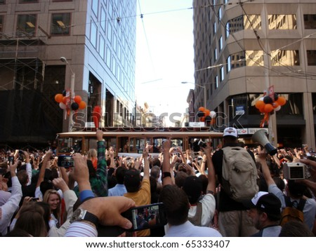 SAN FRANCISCO, CA - NOVEMBER 3: Giants fans celebrate the passing of trolleys during championship parade with fans waving and taking photos with cameras and cellphones Nov. 3, 2010 San Francisco, CA. - stock photo