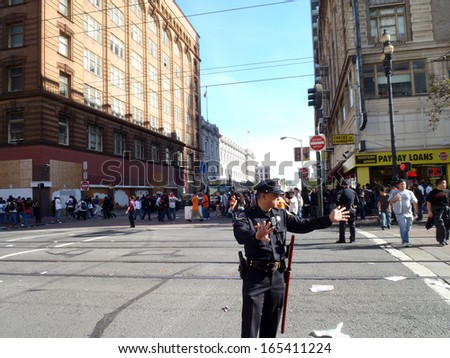 SAN FRANCISCO, CA - NOVEMBER 3: SFPD Police officers holds out hands to wave on crowd on a closed market street to help keeping the order in the area after Parade Nov. 3, 2010 San Francisco, CA. - stock photo