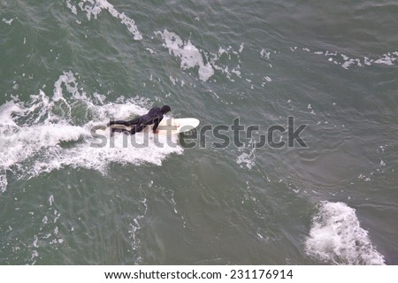 SAN FRANCISCO, CA, USA - APRIL 2010: Aerial View of surfer preparing to get up on the board and ride a wave. San Francisco Bay, California, USA