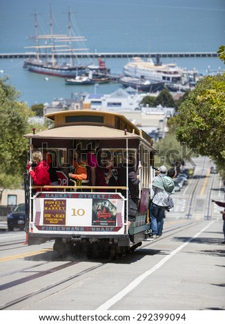 San Francisco, CA, USA - June 23rd, 2015: Tourists riding on a cable car in the Russian Hill district of San Francisco - stock photo