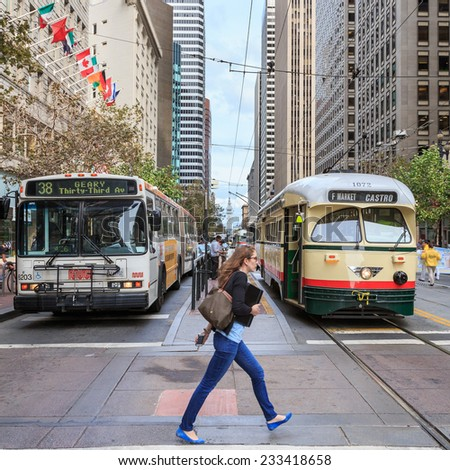 SAN FRANCISCO, CA, USA - OCTOBER 15, 2014: Young woman hurries across intersection as bus and tram wait in San Francisco, CA, USA on October 15, 2014. - stock photo