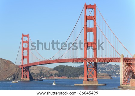 SAN FRANCISCO, CALIFORNIA - NOVEMBER 1, 2010: Golden Gate Bridge taken from Baker Beach on November 1, 2010, as a sailboat passes under bridge. Location is well known location near Golden Gate Park. - stock photo