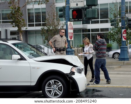 SAN FRANCISCO - JANUARY 16, 2010: Highway Patrol police office assist people after their white BMW SUV is in an accident on King Street in Mission Bay, San Francisco. - stock photo