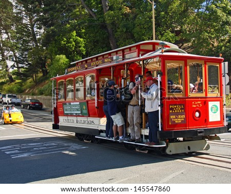 SAN FRANCISCO - JUN 20: Tourists ride a cable care in San Francisco followed by a small touring car. Taken June 20, 2012 in San Francisco, CA. - stock photo