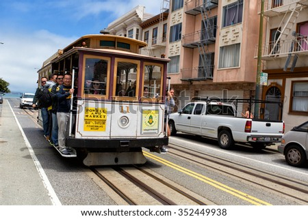 SAN FRANCISCO - JUNE 23, 2015: Passengers enjoy a ride in a cable car on June 23, 2015 in San Francisco. It is the oldest mechanical public transport in San Francisco which is in service since 1873. - stock photo