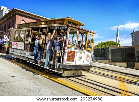 SAN FRANCISCO - OCT 06: Passengers enjoy a ride in a cable car on Oct 06, 2012 in front of famous Transamerica building in San Francisco. Oldest mechanical public transport. In service since 1873.  - stock photo