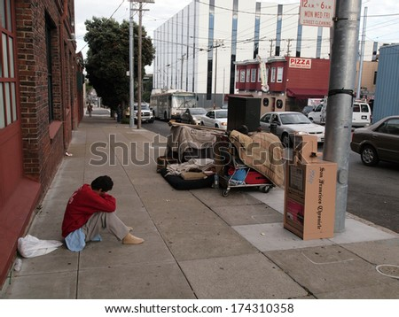SAN FRANCISCO - OCTOBER 5: Homeless man sits on sidewalk with shopping carts full of his stuff on the other side of sidewalk in the Mission part of San Francisco California  October 5, 2010. - stock photo