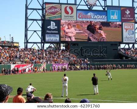 SAN FRANCISCO - OCTOBER 2: Padres vs. Giants: Woman wins house on big screen as Giants Barry Zito warms up before game.  taken on October 2 2010 at Att Park in San Francisco California. - stock photo