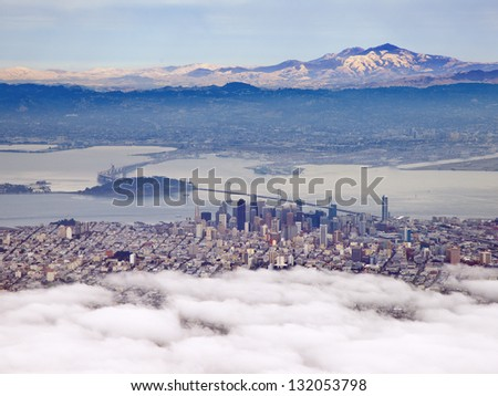 San Francisco shrouded in fog with Mt Diablo in the distance - stock photo
