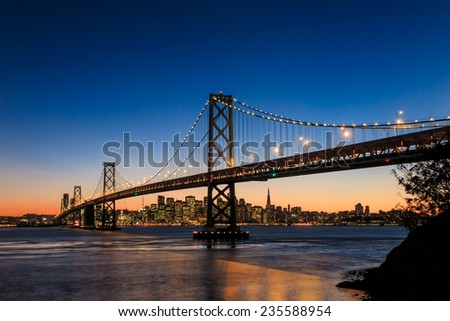 San Francisco skyline and Bay Bridge at sunset, California USA - stock photo