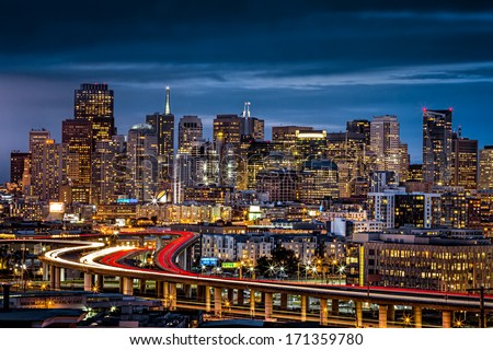 San Francisco skyline. Fog ready to come down over the city as the sun is waving goodbye for the day behind the clouds. - stock photo