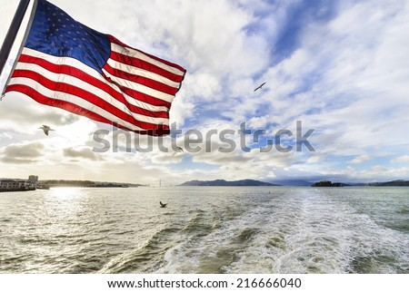 SAN FRANCISCO,USA - FEBRUARY 28,2014: View of San Francisco Bay,the Golden Gate bridge,seagulls flying,the american flag waving and Alcatraz island at sunset from a ferry in California, United States. - stock photo