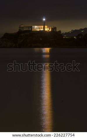SAN FRANCISCO,USA - MARCH 1 2014: The Alcatraz Penitentiary island in California,United States of America.Night view of light reflected in the sea from the lighthouse,prison buildings and the Bay.