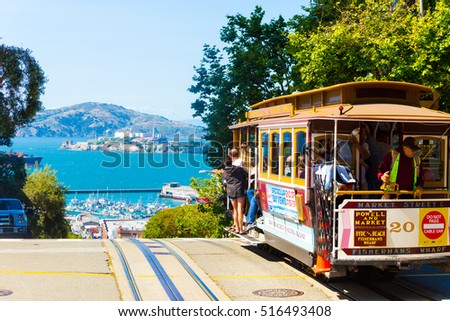San Francisco, USA - May 15, 2016: A cable car full of tourists at the peak of Hyde Street going over the edge toward the view of Alcatraz Island in the SF bay. Horizontal
