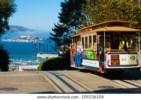 SAN FRANCISCO, USA - SEPTEMBER 21: Powell Hyde cable car, an iconic tourist attraction, descends a steep hill overlooking Alcatraz prison and SF bay on September 21, 2011 in San Francisco, USA - stock photo