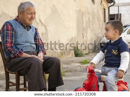 SAN GIMIGNANO, ITALY - APRIL 21:Grandfather on a chair in the street talks to grandchild  in small Italian town  April 21, 2011 in San Gimignano, Italy. The extended family is part of Italian culture. - stock photo