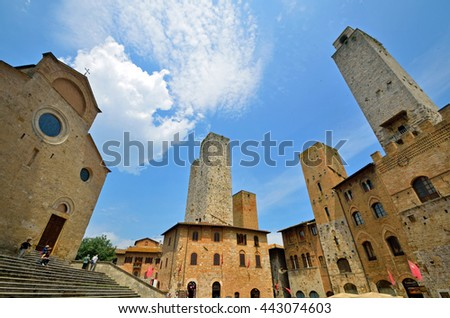 SAN GIMIGNANO, ITALY - JUNE 8 2016: San Gimignano is a walled hill town and there are medieval towers and Basilica Collegiata di Santa Maria Assunta at Piazza del Duomo.