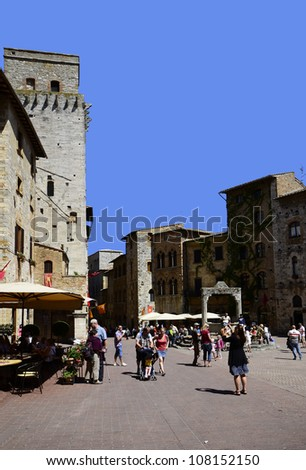 SAN GIMIGNANO, ITALY - JUNE 12: tourists on Piazza Cisterna in the medieval hill town, it is a Unesco World Heritage site in Tuscany, on June 12, 2012 in San Gimignano, Italy
