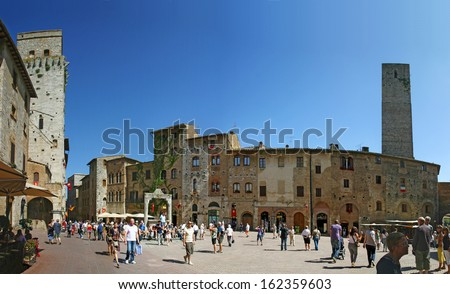 SAN GIMIGNANO, ITALY - JUNE 19: Tourists walk in San Gimignano, Italy, June 19, 2011. The Historic Centre of San Gimignano is a UNESCO World Heritage Site.