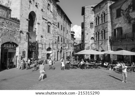 SAN GIMIGNANO, ITALY - 27th of August 2014: Tourists walk in San Gimignano. The  Centre of San Gimignano is a UNESCO World Heritage on 27th of August 2014 in SAN GIMIGNANO, ITALY (black and white) - stock photo