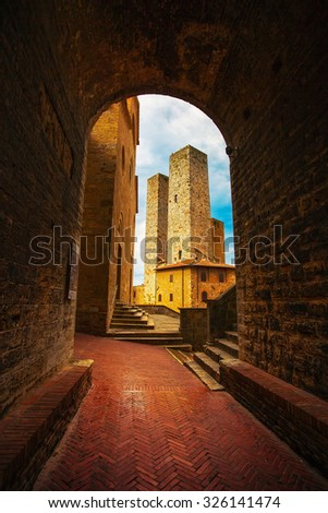 San Gimignano landmark medieval town. Sunset from a tunnel on towers in central Erbe Square. Tuscany, Italy, Europe. - stock photo
