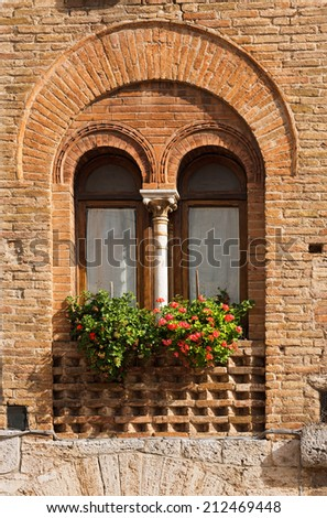 San Gimignano - Siena Tuscany Italy / Detail of a mullioned window on medieval brick wall in San Gimignano town (UNESCO heritage), Siena, Tuscany, Italy - stock photo